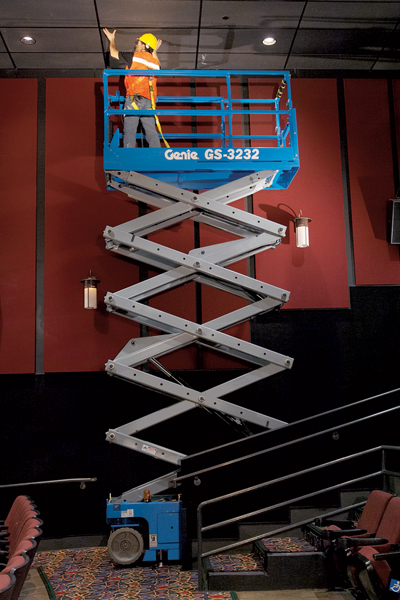 Genie electric scissor lift GS-3232 with inline outriggers working in a cinema