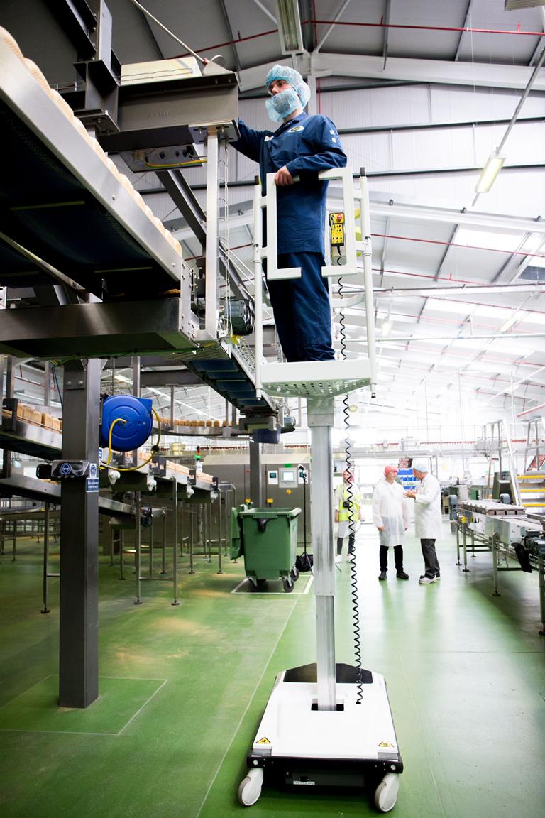 Hugo lift working on conveyor maintenance in factory